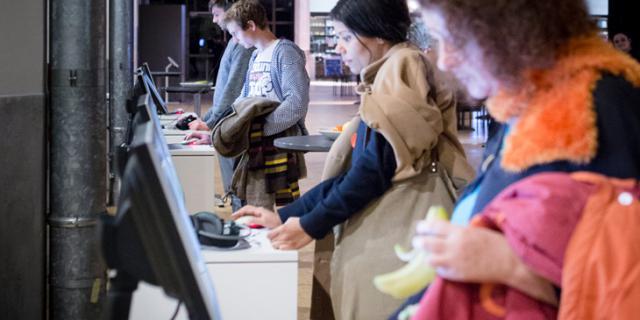 Mehrere Menschen stehen vor Computerstationen