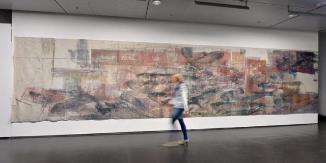 Eine Frau läuft an einem Gemälde vorbei