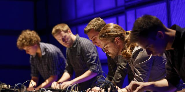 Five young men, very concentrated, in front of a mixer