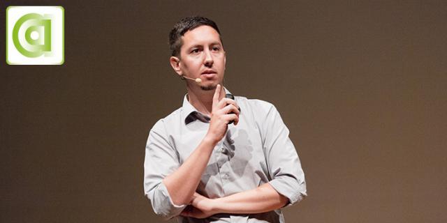 Ein Mann steht auf einer Bühne und spricht
