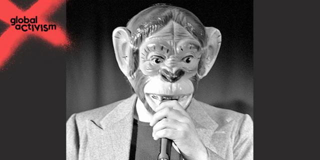 Ein Mann mit einer Affenmaske spricht in eine Mikrofon