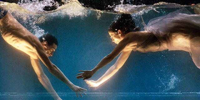 """Ausschnitt aus Sasha Waltz """"Dido & Aeneas"""". Zwei halbnackte Tänzer zeigen eine Choreografie in einem bis zum Bildrand gefüllten Wassertank, welcher von unten beleuchtet wird."""