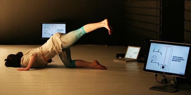 Eine Frau liegt mit dem Oberkörper auf dem Boden uns treckt das linke Bein nach hinten hoch
