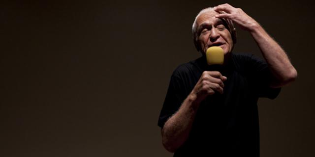 Ein Mann spricht in ein Mirkofon und hält die linke Hand an seinen Kopf