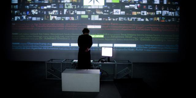Ein Frau steht vor einer Wand mit Projektionen von verschiedenen Bildern und Text in mehreren Farben