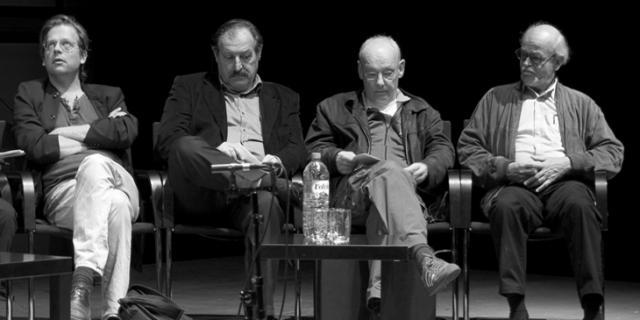 Vier Männer sitzen nebeneinander auf einer Bühne
