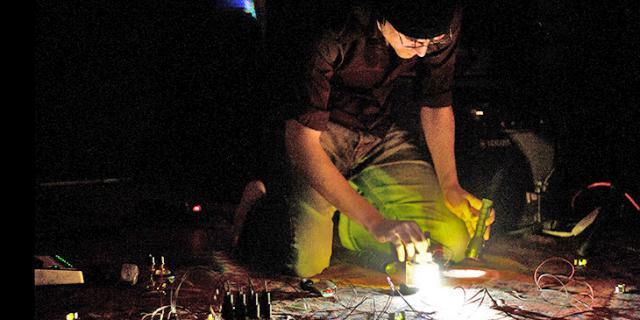 Mann kniet auf dem Boden vor Kabeln und Reglern