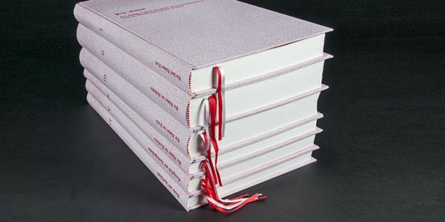 Sechs Bücher mit weißem Umschlag und roter Schrift übereinandergestapelt