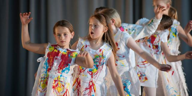 Kinder in bunte bemalten Kittel tanzen