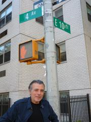 A man standing at an intersection under traffic lights with a red hand on it