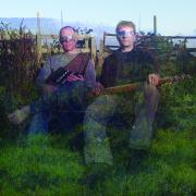 Zwei Männer sitzen mit Musikinstrumenten in der Hand auf einer Wiese, ihre Augen sind mit silbernem Klebeband verhüllt