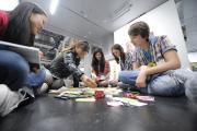 Eine Gruppe von Jugendlichen arbeitet in einer ZKM Ausstellung an ihrer Visualisierung sozialer Netzwerke.