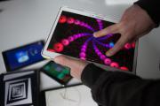 Nahaufnahme: Jemand bedient mit zwei Fingern eine künstlerische App auf einem Tablet. Im Hintergrund liegen weitere Tablets mit unterschiedlichen Apps.