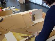 A woman is working on a miniature stage scenery