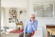 Professor Bude sits on a red chair in an apartment with bookshelf and desk, his head resting on his hand.