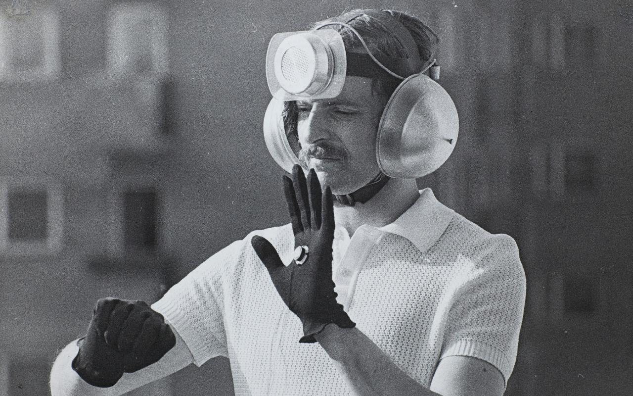 Das Schwarzweiß-Photo zeigt einen Mann mit einer technischen Installation auf dem Kopf, seine Ohren sind mit Schallschützern bedeckt.