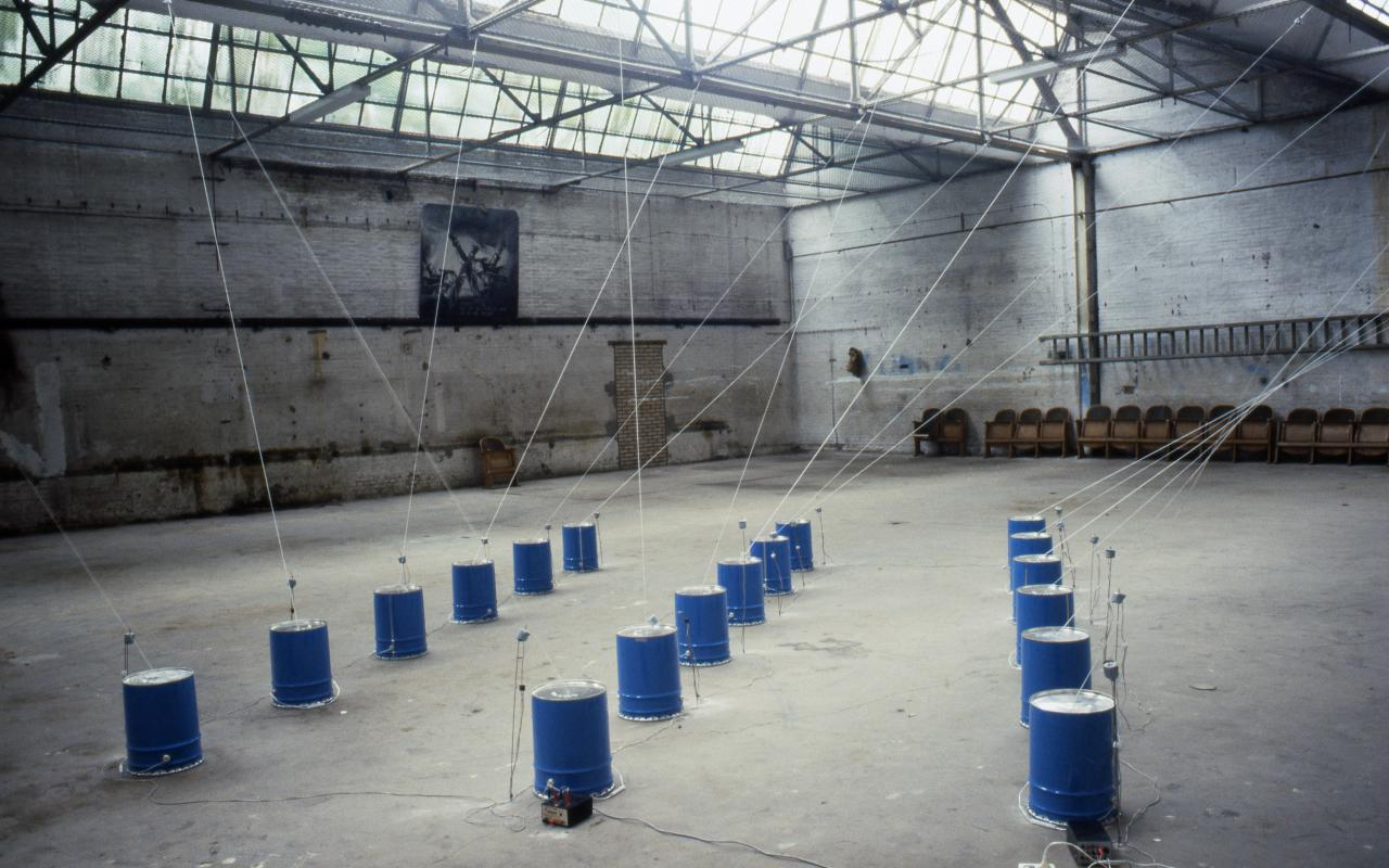 The picture shows an installation by Paul Panhuysen: Several dark blue barrels, from which ropes go to the ceiling, stand in a warehouse.