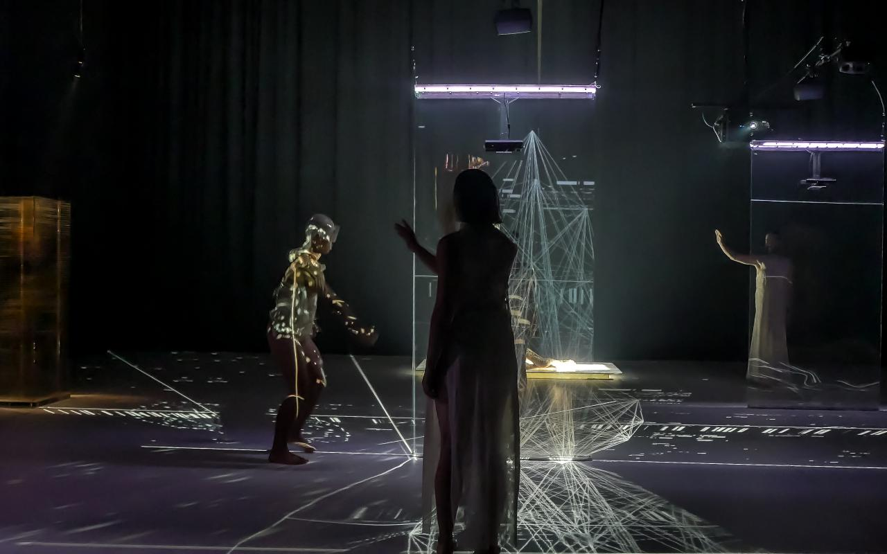 Drei Tänzer stehen auf der Bühne, es ist dunkel. In der Mitte der Bühne ist eine Installation aus Laserlicht. Auf dem Körper des linken Tänzers ist ein projiziertes Lichtspiel.