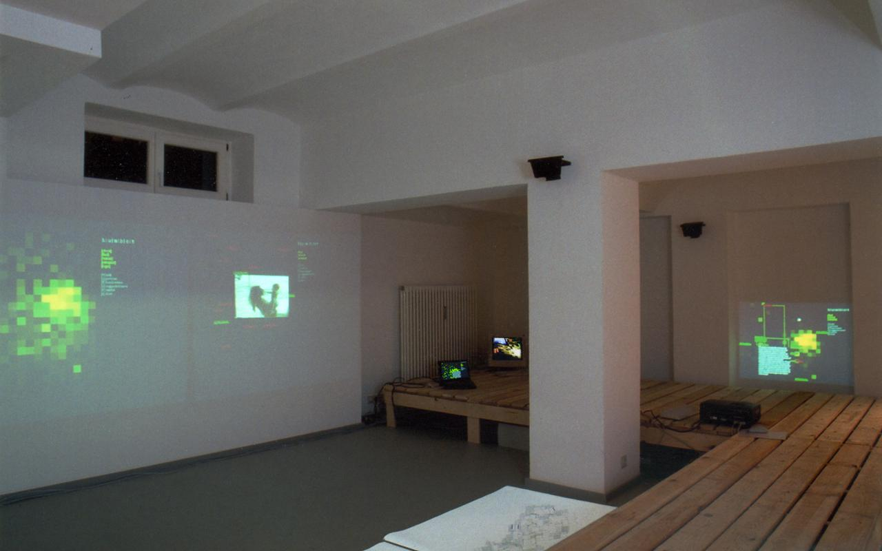 Blick in den Ausstellungsraum der Galerie K & S: In einer Raumarchitektur aus Paletten werden Landkarten, Bilder und Filme projiziert.