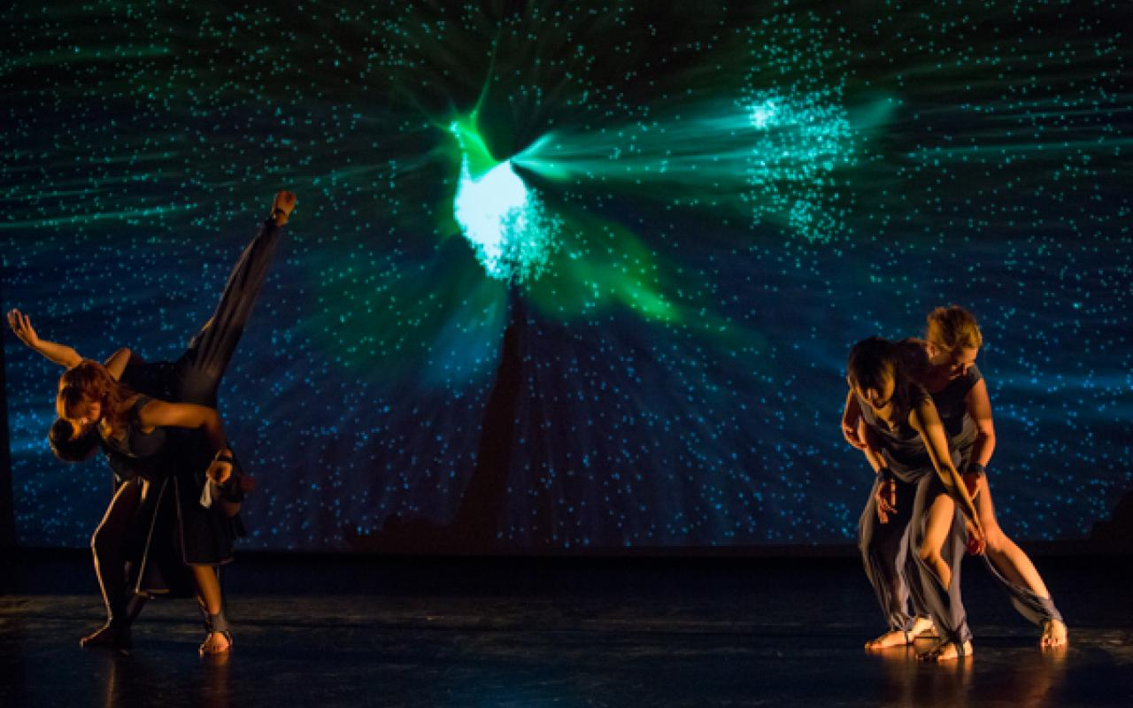 Four dancers in the foreground, in the background a starry sky with a bird-like structure.