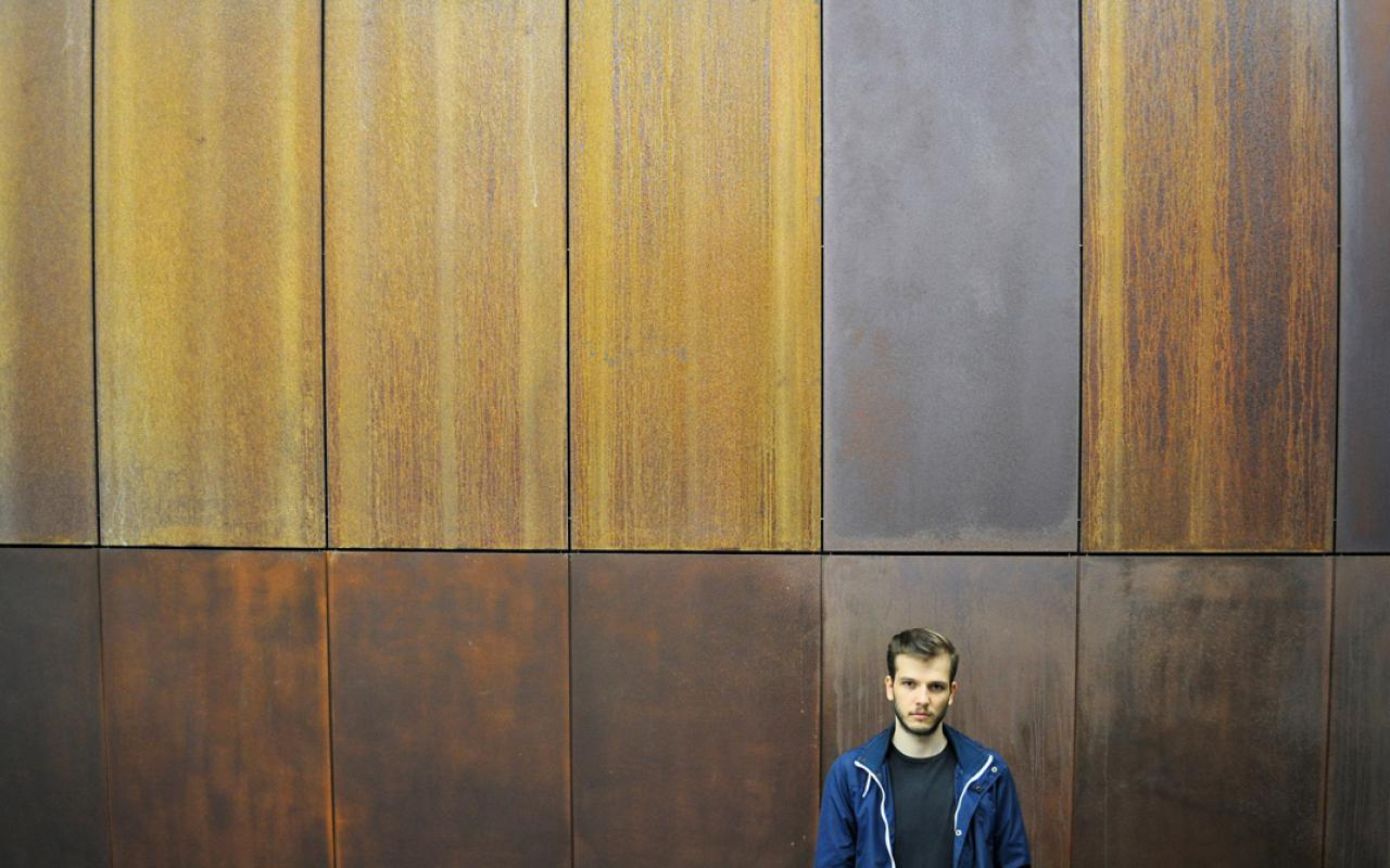 A young man wearing blue sports jacket standing in front of a wooden wall