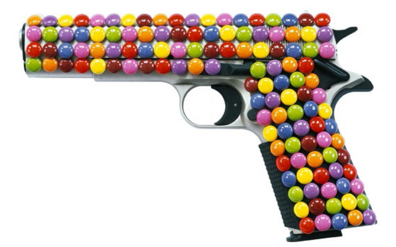 Eine Pistole ist ganz von Smarties umhüllt.
