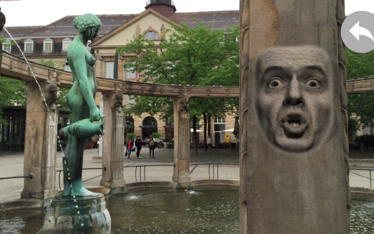 View of the fountain at Stefansplatz: on the column the projection of a speaking, male face.