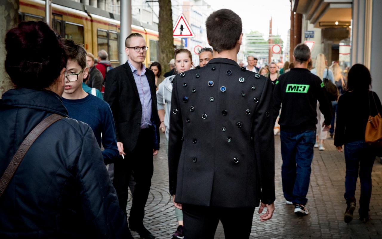 Ein Mann mit einer Jacke, die mit Kameralinsen gespickt ist