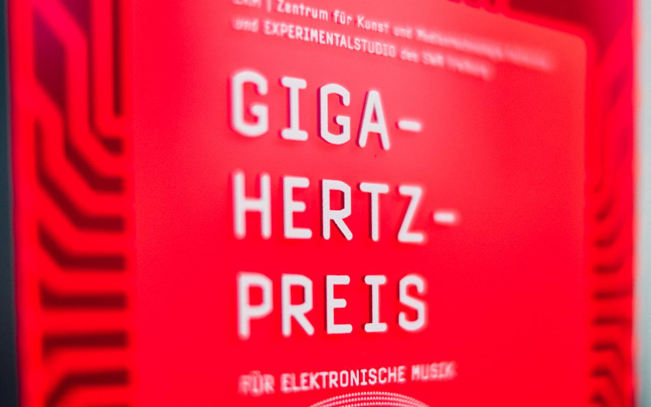 """Red plaque with """"Giga-Hertz-Award"""" in white letters"""