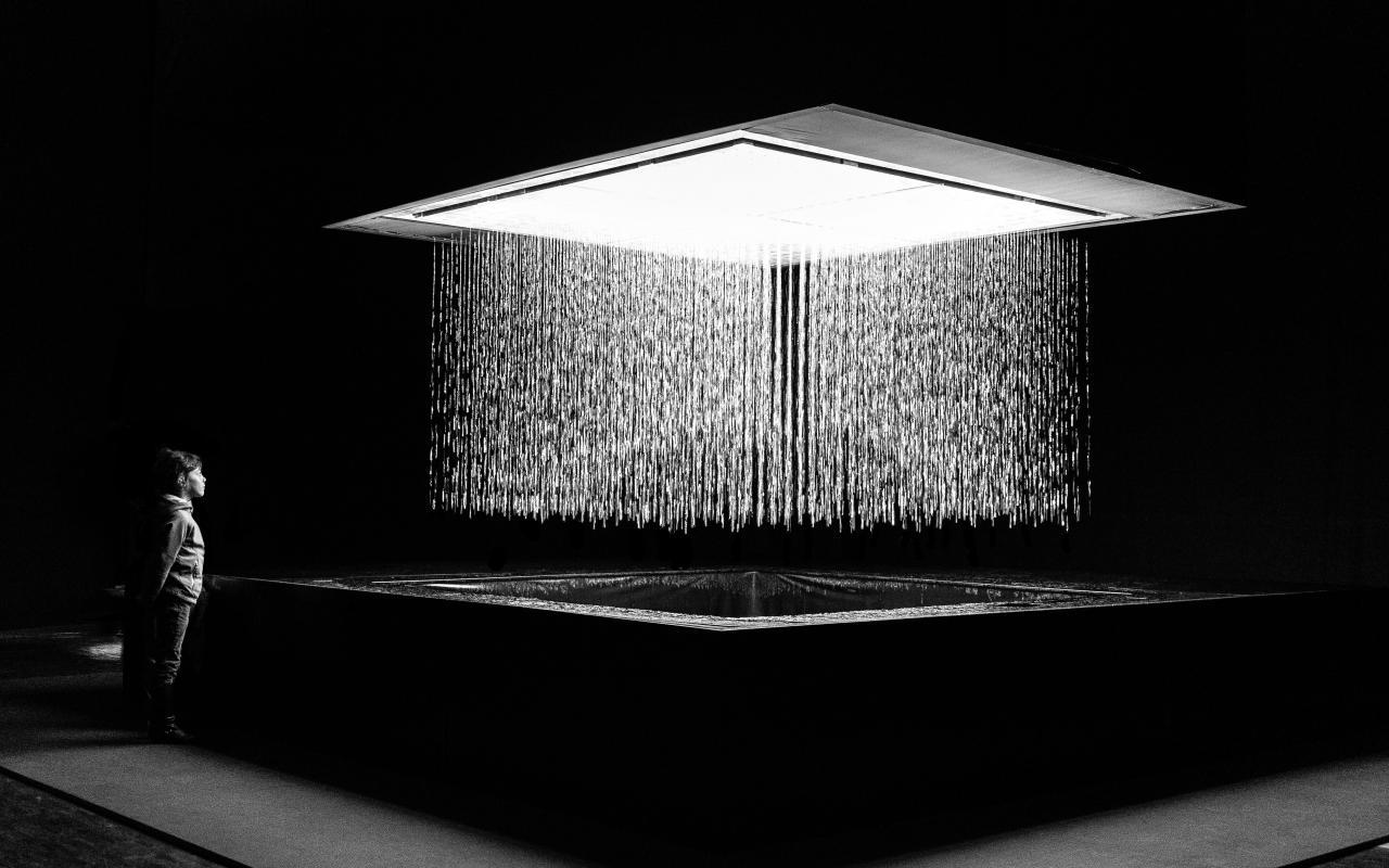 Schwarzweißaufnahme der Installation 3D WATERMATRIX, die Wasser formgebend von der Decke zum Boden fallen lässt. Eine Person betrachtet die Installation.