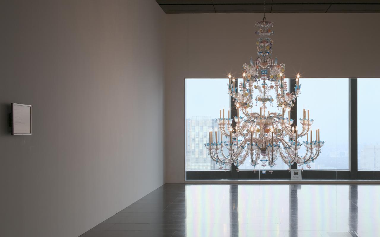 Illuminated chandelier in empty room in front of large windows.