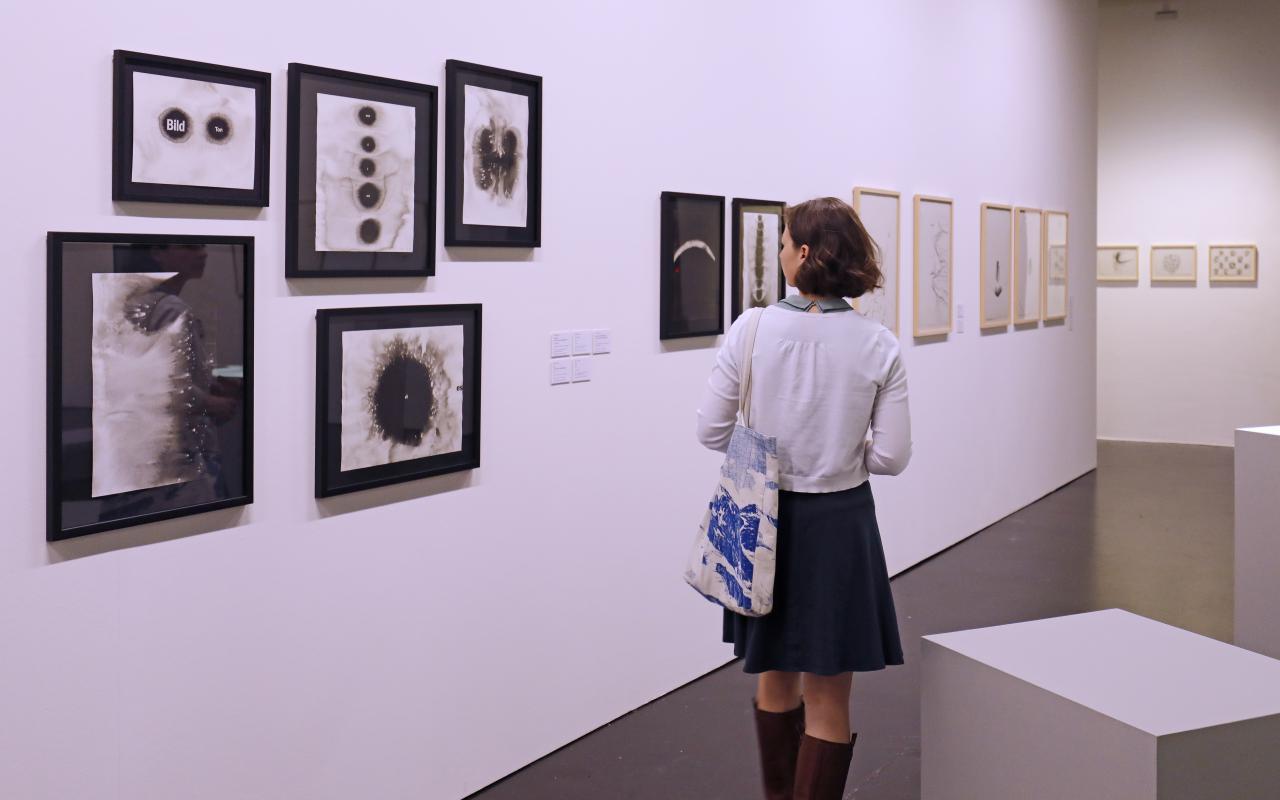 Eine junge Frau betrachtet Collagen Gerhard Rühms.