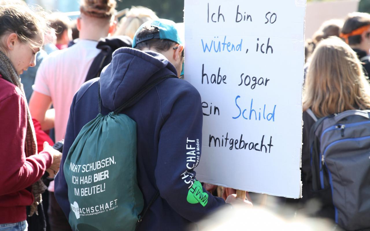 """Zu sehen ist ein Ausschnitt einer Menschenmenge und ein Plakat mit der Aufschrift """"Ich bin so wütend, ich habe sogar ein Bild mitgebracht!"""""""