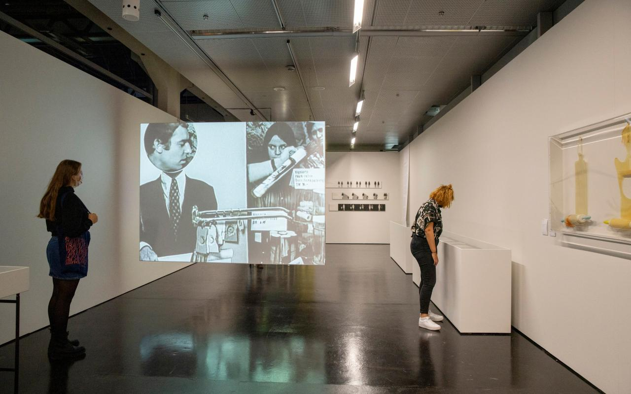 Two young women in the exhibition space. One is standing on the left wall and the other is looking at the right wall in showcases. A screen is stretched between them, on which a film clip with people can be seen.