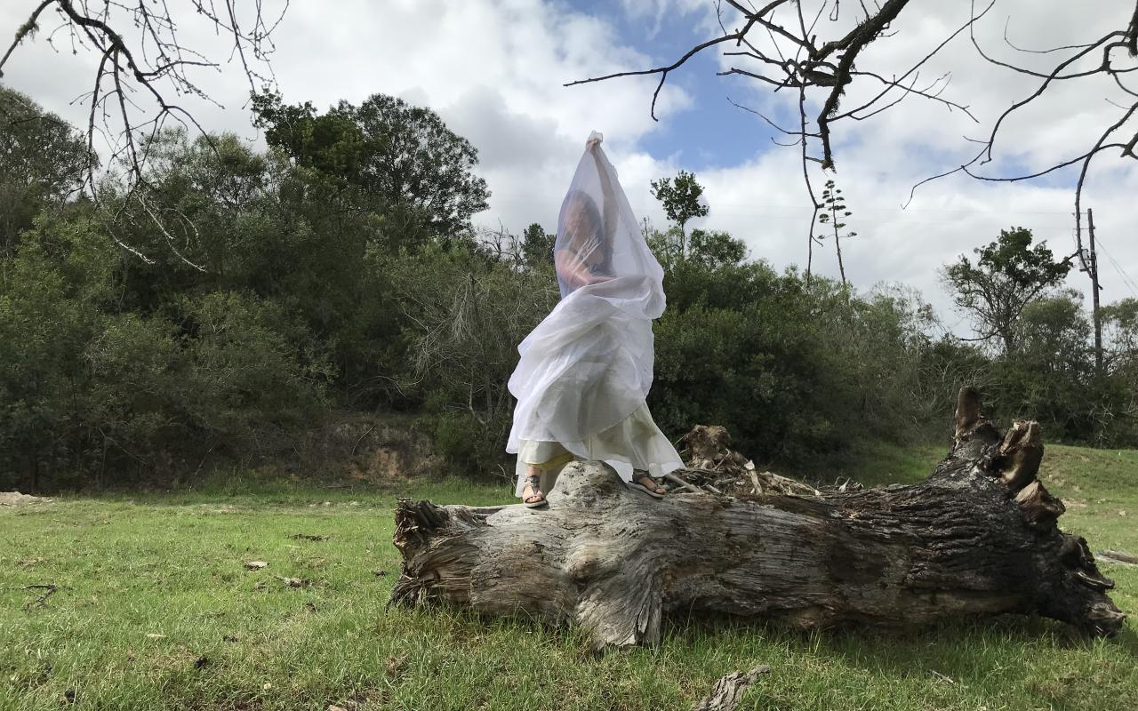 A woman wrapped in white cloth stands on a large piece of deadwood in the middle of a clearing.