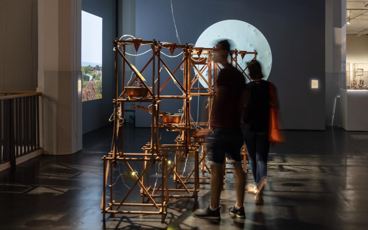 Zu sehen ist eine Installation aus Holzstriemen, in der auf mehreren Ebenen Wasser von einer Schale zur nächsten gelangen kann. Von oben tropft das Wasser ebenfalls in die Schalen.