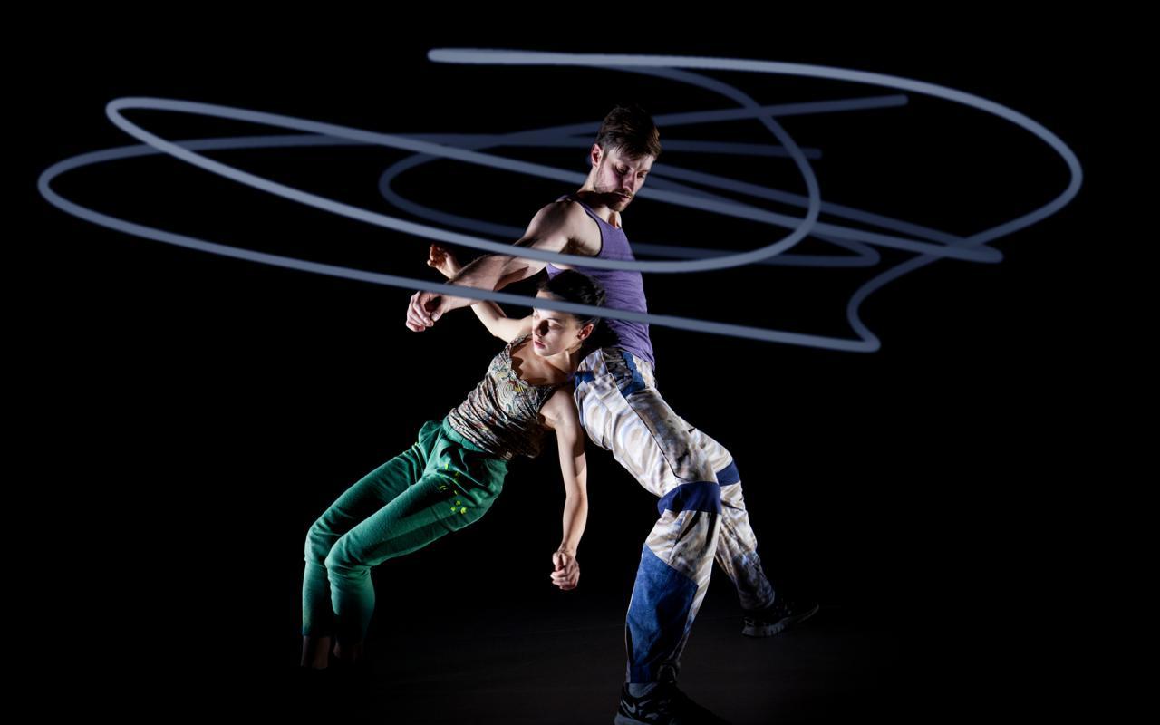 Zwei Tänzer vor schwarzem Hintergrund, umhüllt von kreisrunden Lichtkunststrahlen