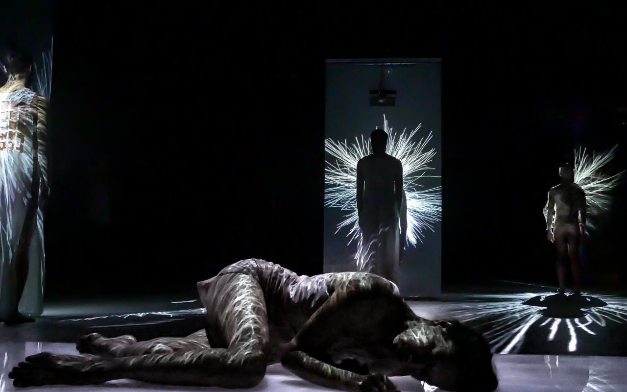 Vier Tänzer sind auf der Bühne, es ist dunkel. Eine Tänzerin liegt vorne an der Bühne, die anderen stehen entfernt zu je einer Himmelsrichtung. Auf allen TänzerInnen sieht man zahlreiche Lichtfäden projiziert.