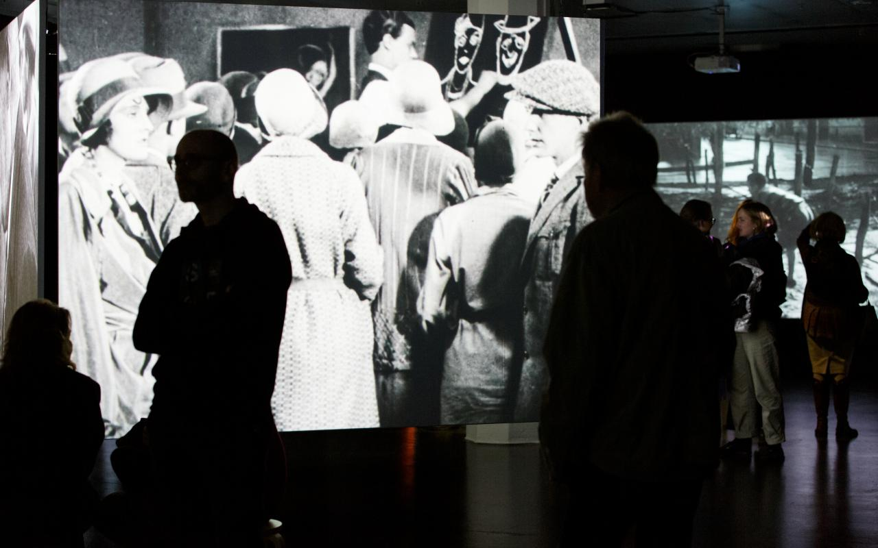 The photo shows the exhibition room with a large projection of a black and white film.
