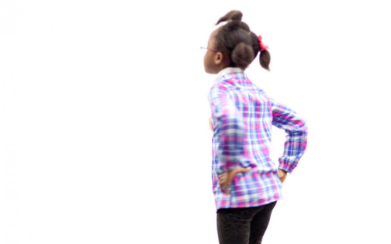 Ein Mädchen hüpft vergnügt in die Luft. Sie dreht dem Betrachter den Rücken und stemmt beide Hände in die Hüfte.