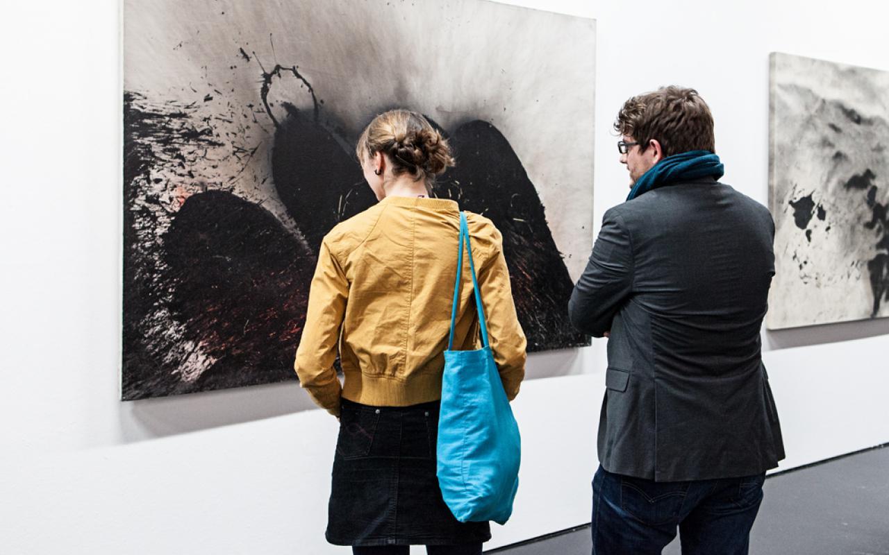 Zwei Personen stehen vor Bildern Otto Pienes.