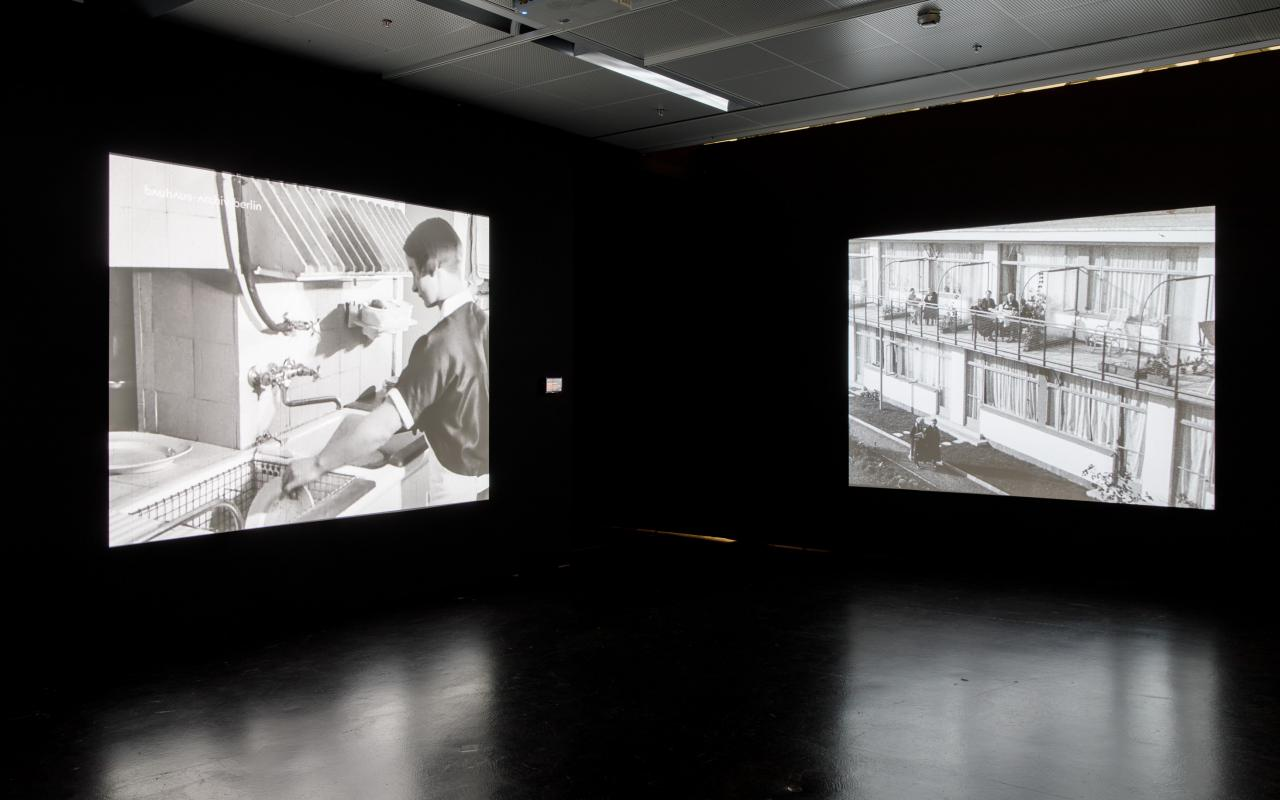 The photo shows the exhibition room with two large screens left and right on the walls. The left canvas shows a woman doing the dishes, the right canvas shows a retirement home from outside and people sitting on balconies.