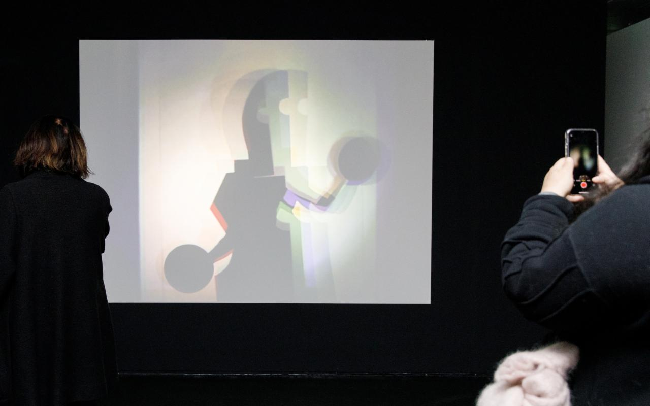 The photo shows a large white canvas on which a Bauhaus figure can be seen.