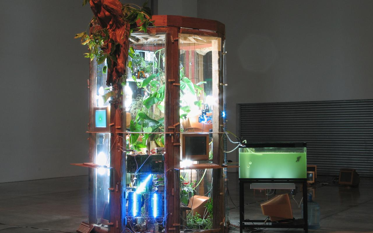 In a type of greenhouse, that is illuminated by spotlights from the inside, are lots of plants and computers. Next to it is an aquarium that is connected to the greenhouse by tubes. At the Rim of the glasshouse there is a wooden figurehead.