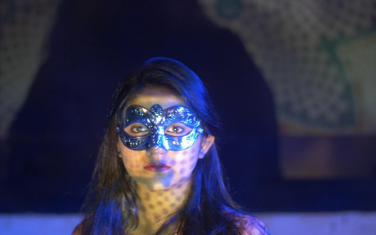 Der Hintergrund ist nebelig, im Vordergrund steht eine junge Frau mit langen Haaren, die eine Maske nach Venezianischer Art trägt.