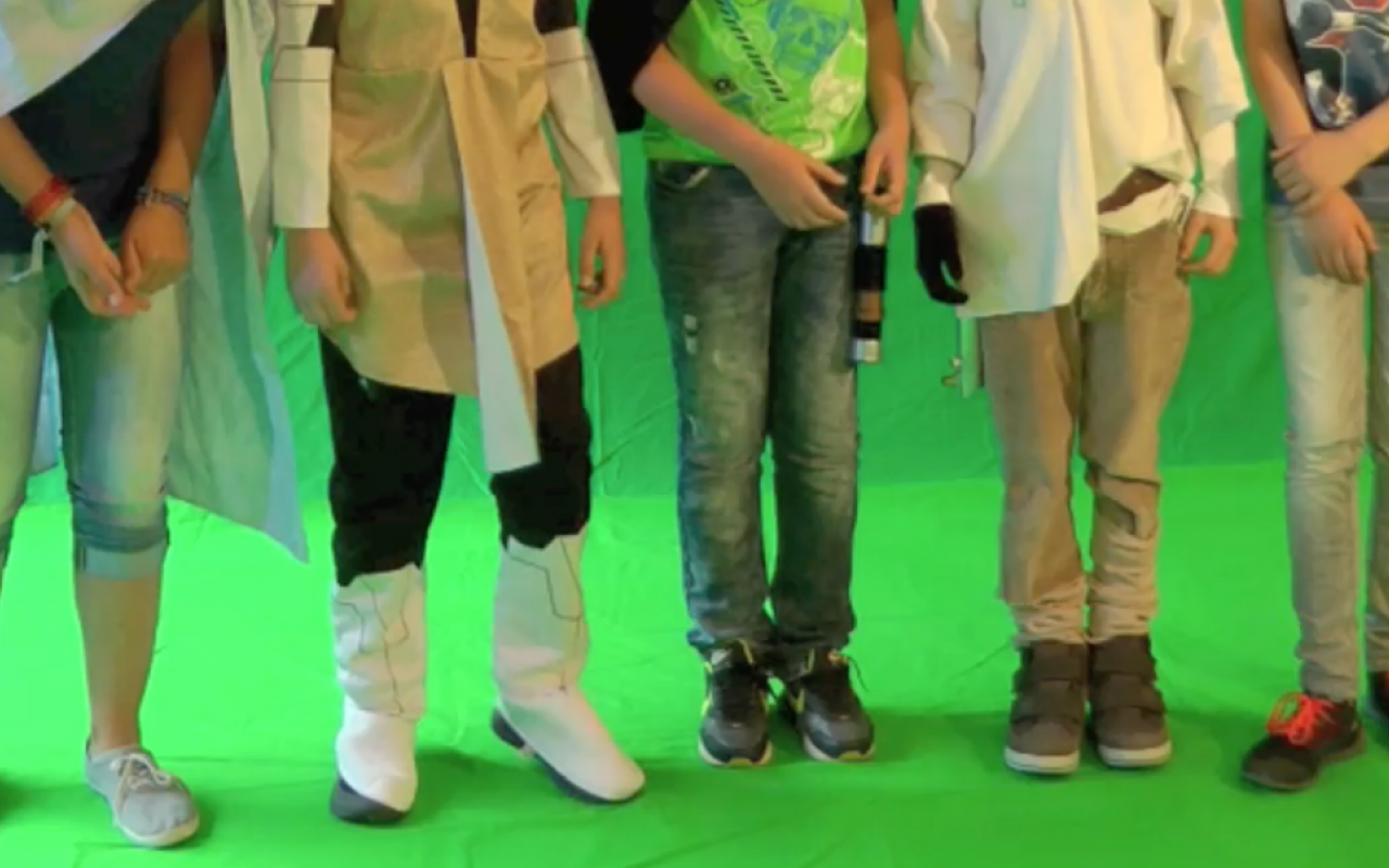 Five kids are standing in front of a greenscreen - only their legs are visible