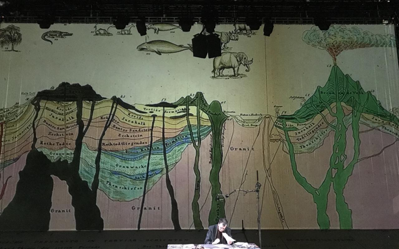 Bruno Latour sitzt auf einer Bühne an einem Schreibtisch. Hinter ihm ist eine Leinwand mit einem geowissenschaftlichen Bild.