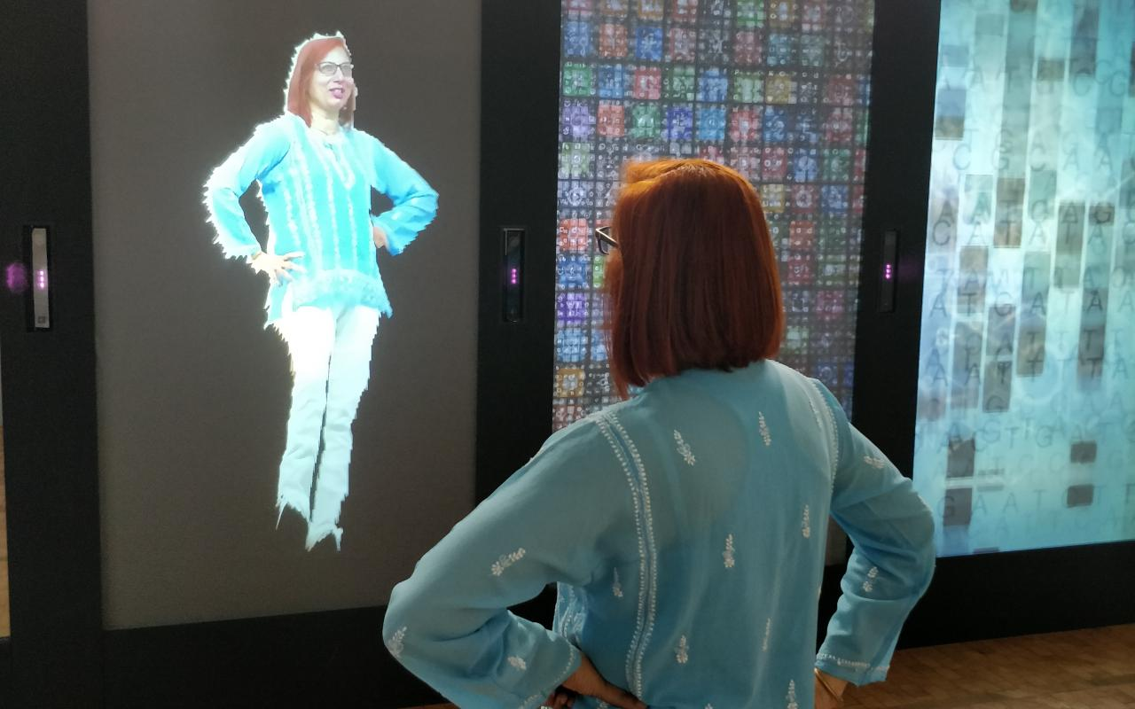 A woman faces her digital reflection