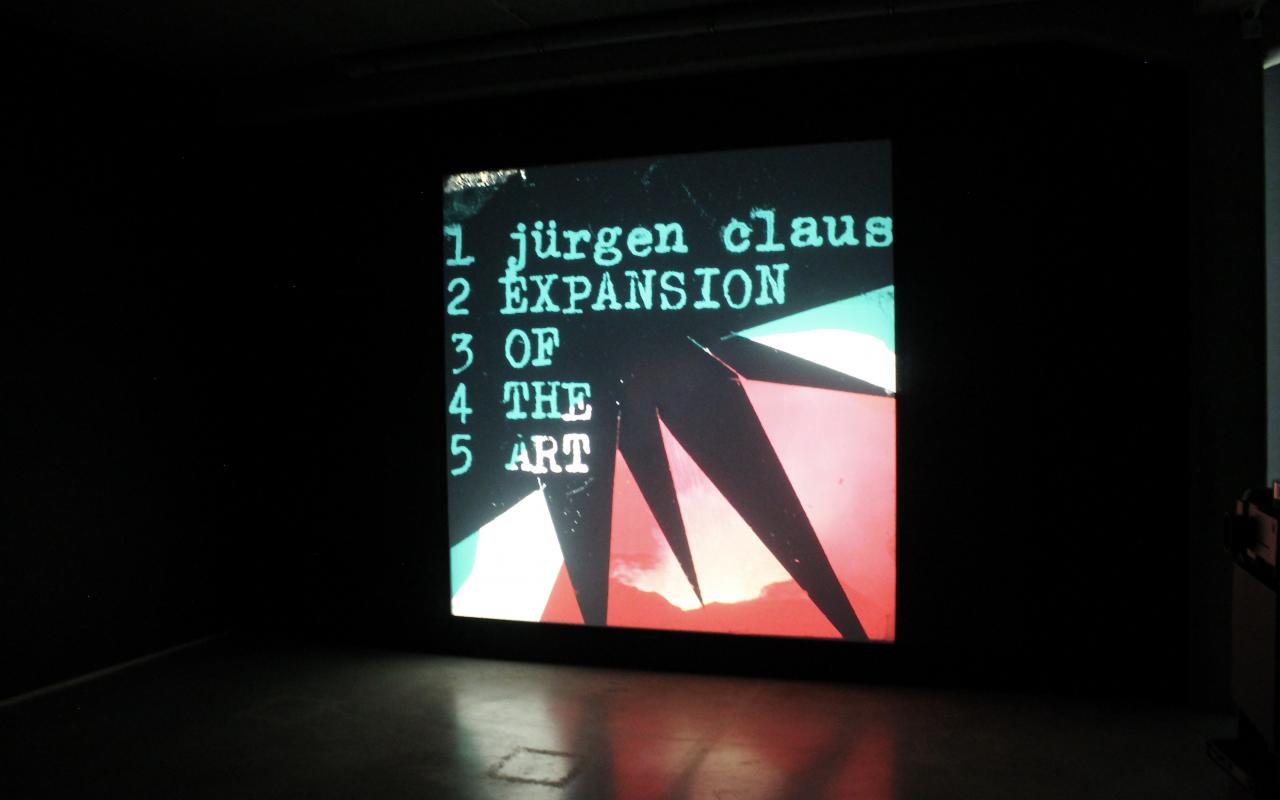 Photo of a multimedia projection, an image in pink, black and turquoise with geometric shapes. On it the text: »Jürgen Claus, Expansion of the Art«