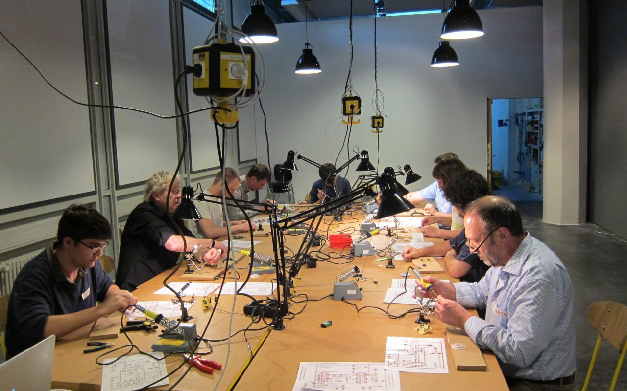 An einem riesigen Tisch sitzen viele Workshopteilnehmer, die mit Lötkolben arbeiten und es liegt allerlei Material kreuz und quer herum.